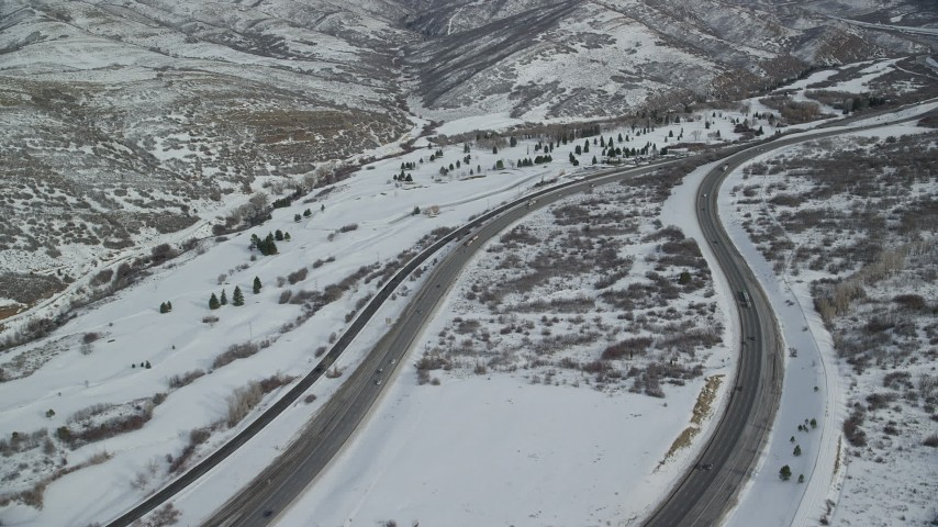6K stock footage aerial video of flying over Interstate 80 with light traffic through snowy Wasatch Range, Utah Aerial Stock Footage | AX126_076