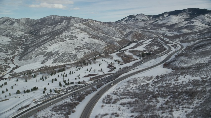 6K stock footage aerial video approach freeway through snowy mountain pass in winter, Utah Aerial Stock Footage | AX126_077