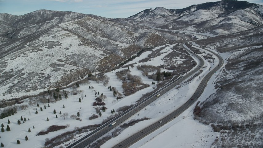 6K stock footage aerial video fly over freeway through snowy mountain pass in winter, Wasach Range, Utah Aerial Stock Footage | AX126_078