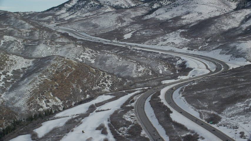 6K stock footage aerial video approach bend in freeway through snowy mountain pass in Utah's Wasatch Range Aerial Stock Footage | AX126_079