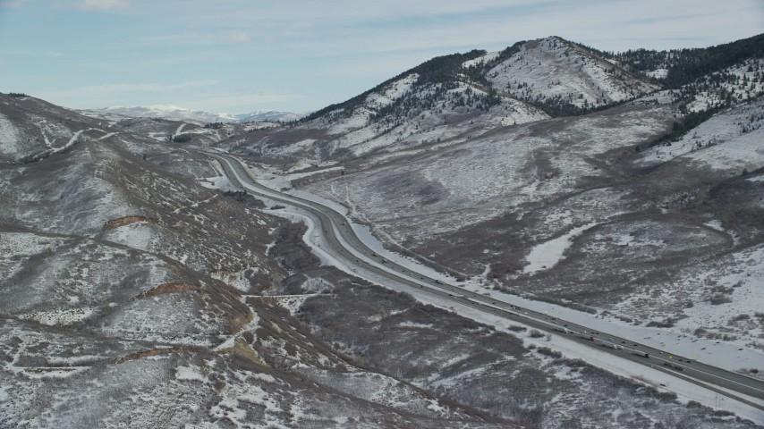 6K stock footage aerial video pan across freeway through snowy mountain pass in winter, Wasatch Range, Utah Aerial Stock Footage | AX126_081