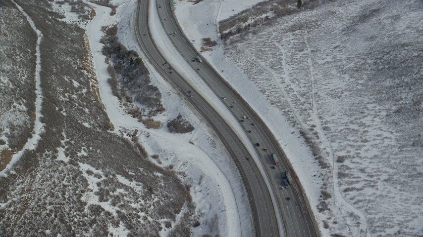 Bird's Eye View of Light Traffic on Mountain Pass Freeway in Winter Aerial Stock Footage | AX126_083