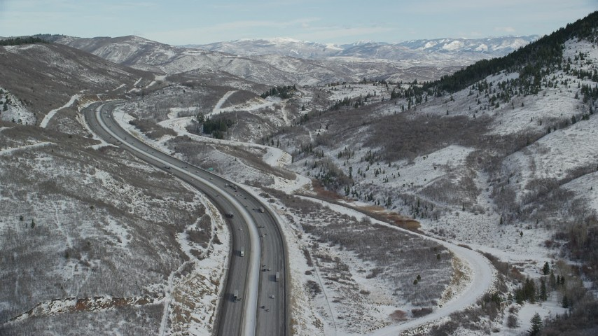 Fly Over Freeway with Light Traffic through Wintery Mountain Pass with Snow Aerial Stock Footage | AX126_084