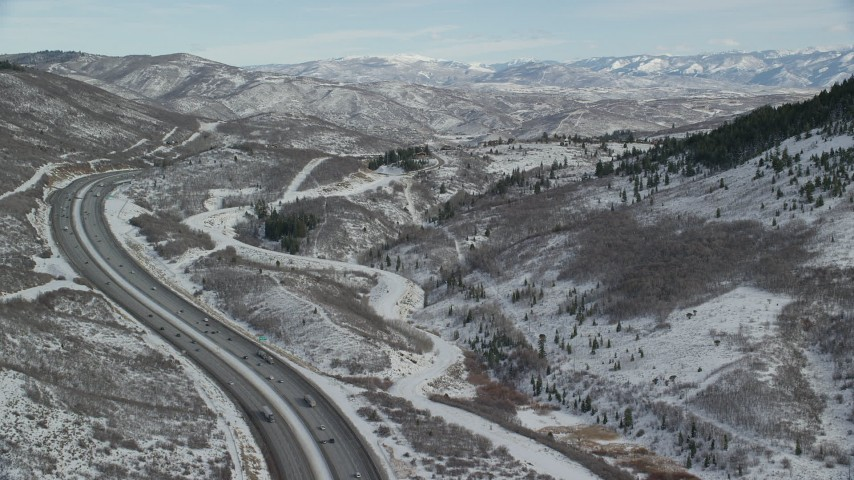 6K stock footage aerial video fly over mountain pass freeway to approach snowy foothills in winter, Wasatch Range, Utah Aerial Stock Footage | AX126_085