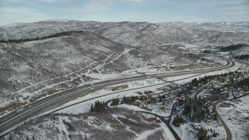 6K stock footage aerial video approach Interstate 80 with light traffic through Park City, Utah Aerial Stock Footage | AX126_086
