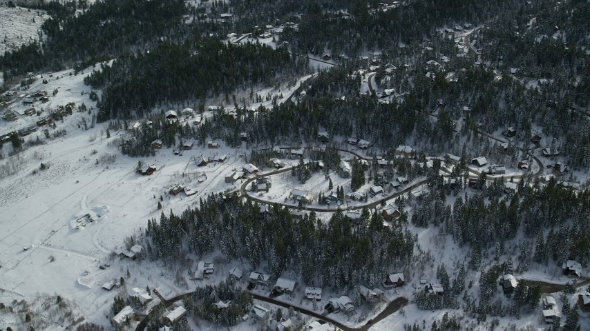 Orbit Upscale Homes and Evergreen Trees Covered in Winter Snow in Park City, Utah Aerial Stock Footage | AX126_088