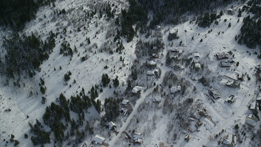 6K stock footage aerial video of orbiting above upscale homes and evergreens with winter snow, Wasatch Range, Utah Aerial Stock Footage | AX126_089