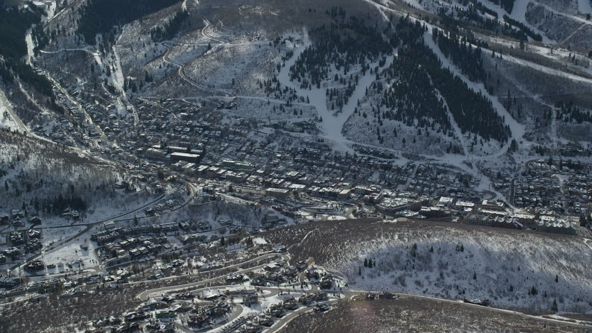 6K stock footage aerial video orbit small town in winter shaded by snowy mountain, Park City, Utah Aerial Stock Footage | AX126_150