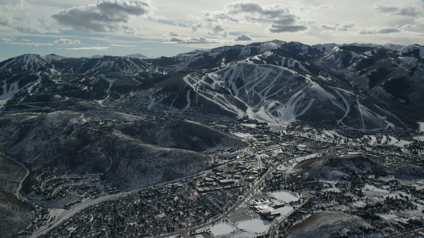 6K stock footage aerial video of reverse view of Park City Mountain Resort slopes beside the town in winter, Utah Aerial Stock Footage   AX126_152