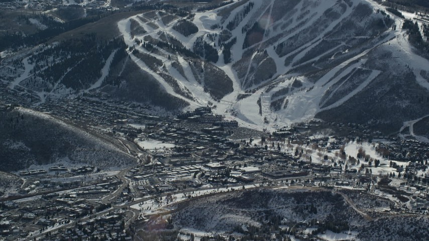 6K stock footage aerial video of snowy ski runs beside a small town in winter, Park City, Utah Aerial Stock Footage   AX126_154