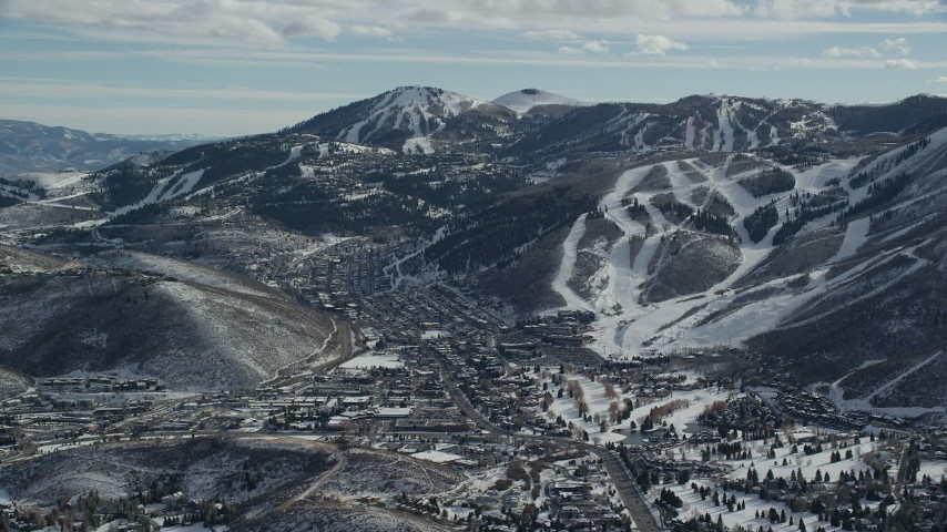 6K stock footage aerial video orbit small town between snowy hills and mountains in winter, Park City, Utah Aerial Stock Footage | AX126_159