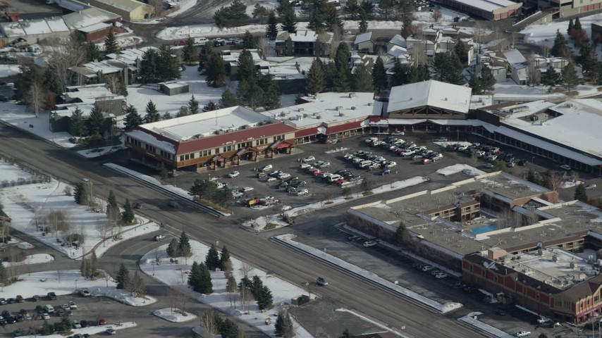 6K stock footage aerial video orbit small town strip mall with winter snow in Park City, Utah Aerial Stock Footage   AX126_163
