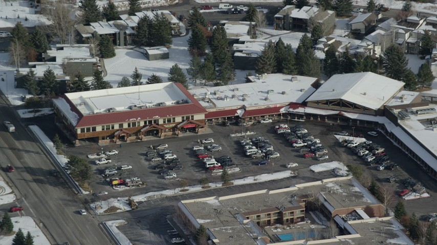 6K stock footage aerial video of orbiting shops at a small town strip mall with winter snow in Park City, Utah Aerial Stock Footage | AX126_164