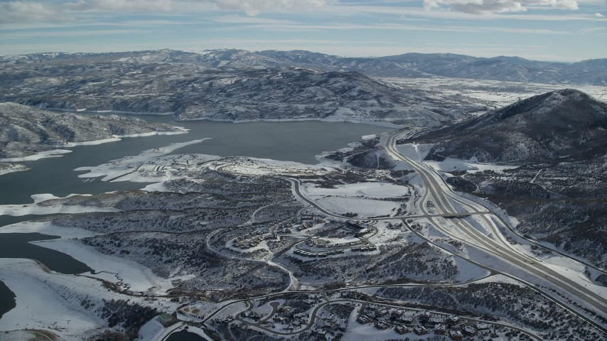 6K stock footage aerial video approach condos and highway near the shore of Jordanelle reservoir with winter snow, Heber City, Utah Aerial Stock Footage | AX126_178