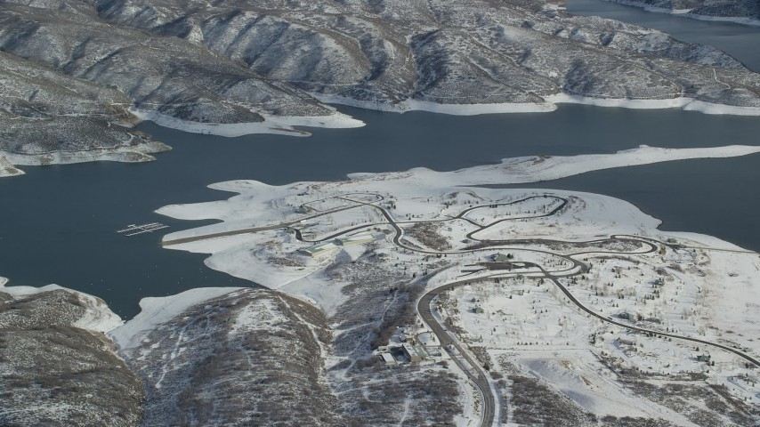 6K stock footage aerial video orbit roads on the shore of the Jordanelle Reservoir in wintertime, Heber City, Utah Aerial Stock Footage | AX126_180