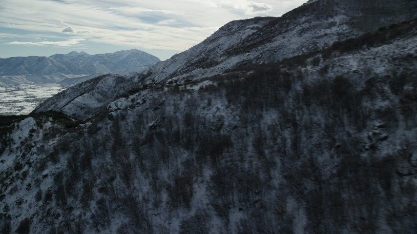 Pan and Fly Over Snowy Wasatch Range Mountain Ridge in Winter Aerial Stock Footage | AX126_189