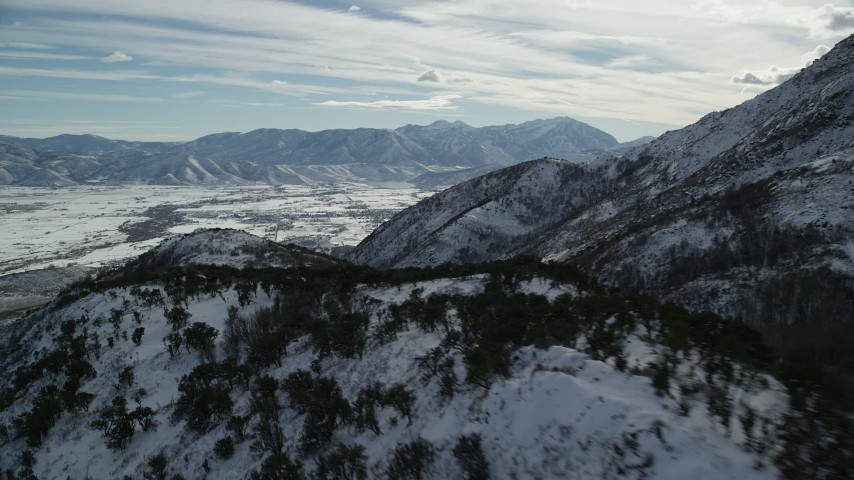 6K stock footage aerial video pan and fly over snowy Wasatch Range mountain ridge in winter, Utah Aerial Stock Footage | AX126_189