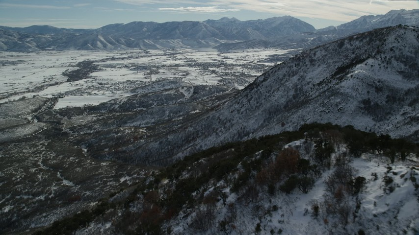 Fly Over Snowy Wasatch Range Slopes to Approach Heber Valley, Utah Aerial Stock Footage   AX126_195