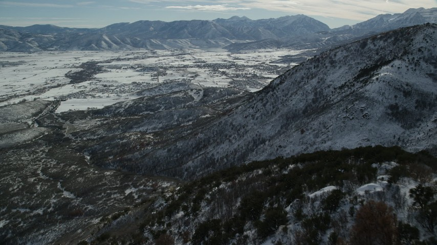 6K stock footage aerial video fly over snowy Wasatch Range slopes to approach Heber Valley, Utah Aerial Stock Footage | AX126_195
