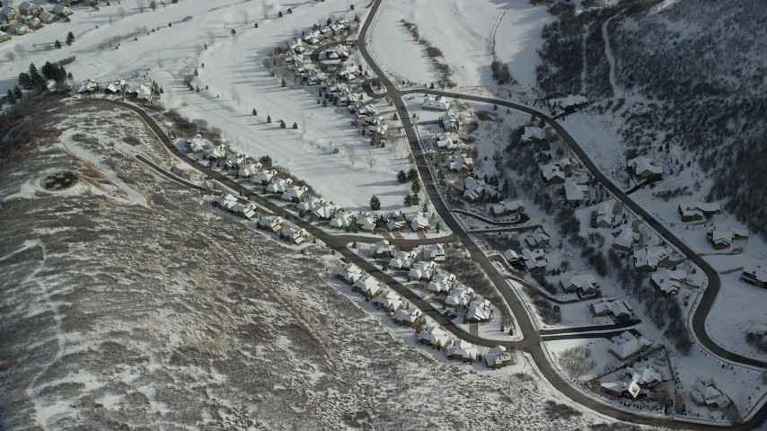 Orbit Tract Homes with Snow in the Shadow of a Peak in Midway Aerial Stock Footage | AX126_204