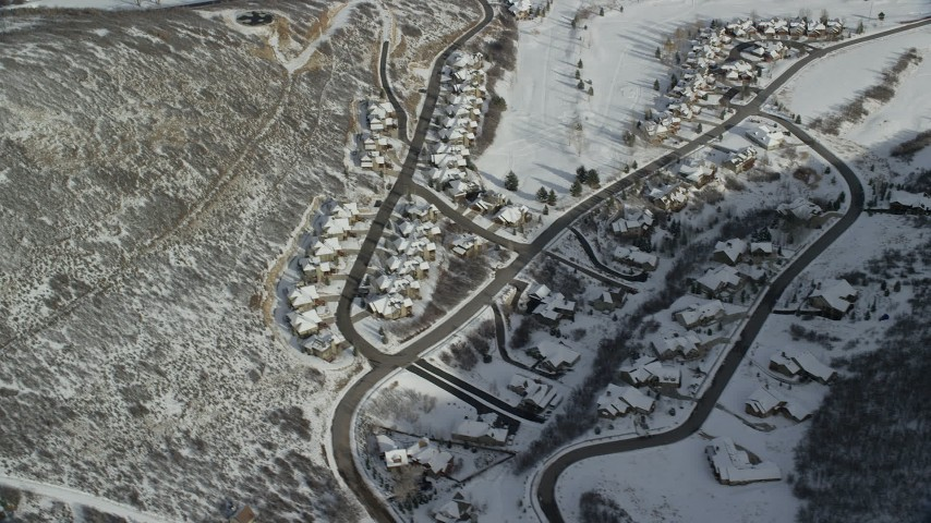 Orbit Snowy Neighborhood with Tract Homes in Wintertime  Aerial Stock Footage | AX126_205