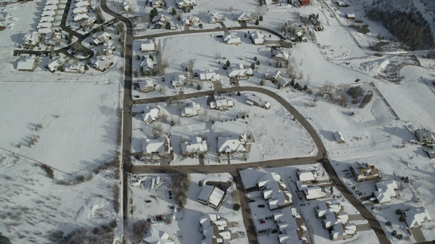 Fly Over Small Residential Neighborhood with Snowy Rooftops in Winter Aerial Stock Footage | AX126_207