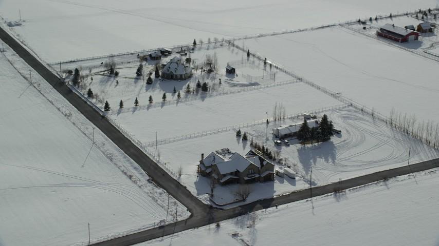 6K stock footage aerial video orbit three large homes by snowy fields in wintertime, Midway, Utah Aerial Stock Footage | AX126_214