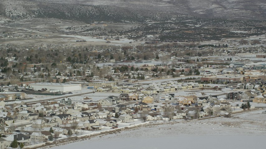 6K stock footage aerial video orbit tract homes by snowy field on outskirts of Heber City in winter, Utah Aerial Stock Footage | AX126_216