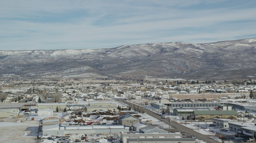 6K stock footage aerial video of mountains with light snow seen from warehouse buildings in winter, Heber City, Utah Aerial Stock Footage   AX126_217