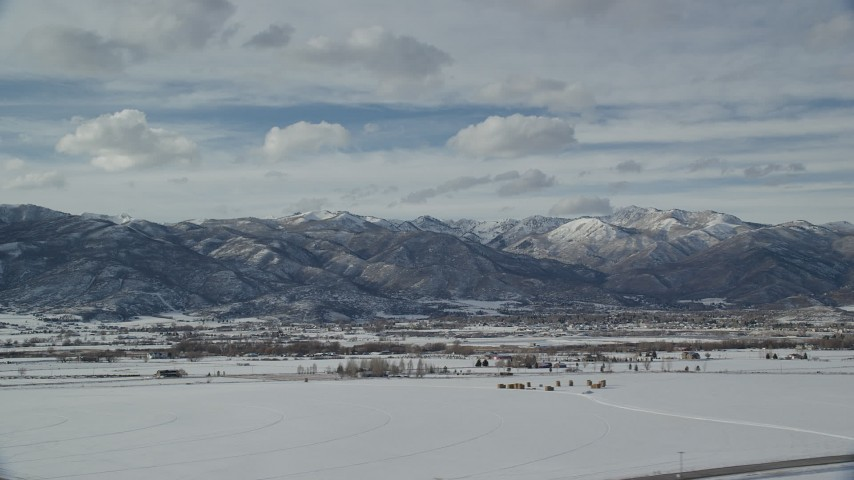 6K stock footage aerial video of small town at the base of snowy mountain range in winter, Heber City, Utah Aerial Stock Footage | AX126_218