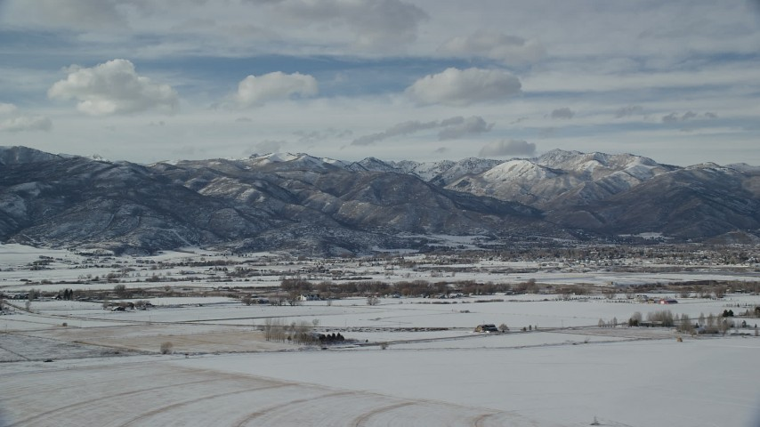 6K stock footage aerial video of snowy fields and mountains around Heber City in winter, Utah Aerial Stock Footage | AX126_219