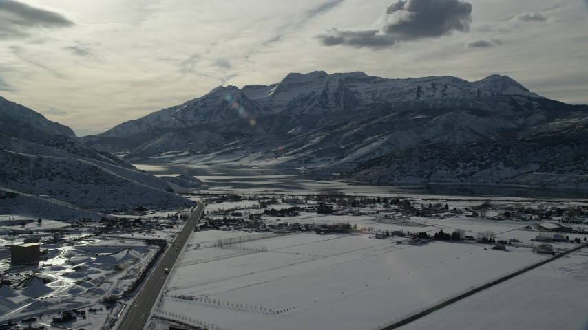 6K stock footage aerial video approach frozen shore of Deer Creek Reservoir and mountains in winter, Heber City, Utah Aerial Stock Footage | AX126_220