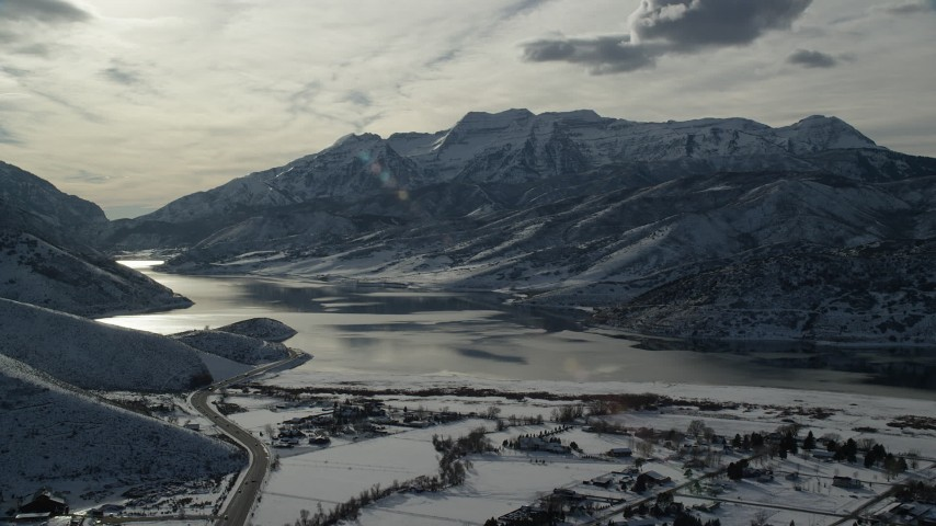 6K stock footage aerial video approach snowy mountains by icy Deer Creek Reservoir in winter, Heber City, Utah Aerial Stock Footage | AX126_222