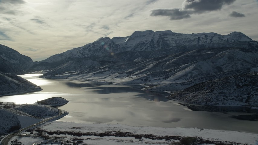 6K stock footage aerial video approach Icy Deer Creek Reservoir and snowy Wasatch Range mountains in winter, Utah Aerial Stock Footage | AX126_223