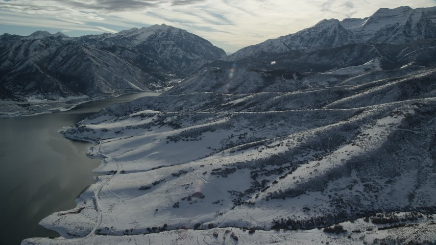 6K stock footage aerial video approach snowy foothills of tall mountains on reservoir shore, Wasatch Range, Utah Aerial Stock Footage | AX126_229