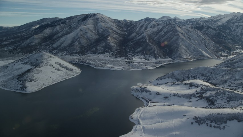 Orbit Icy Reservoir with Snowy Mountains on the Shore in Winter Aerial Stock Footage | AX126_230