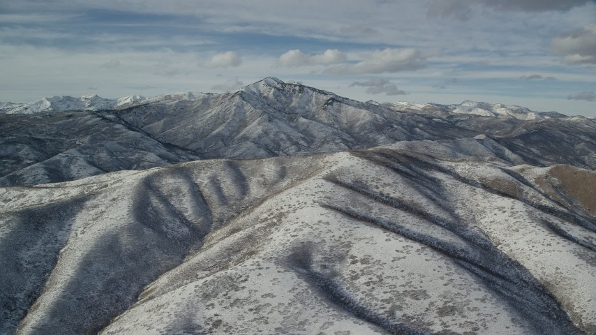 6K stock footage aerial video orbit snowy Wasatch Range mountain with giant peak in the far distance, Utah Aerial Stock Footage | AX126_233
