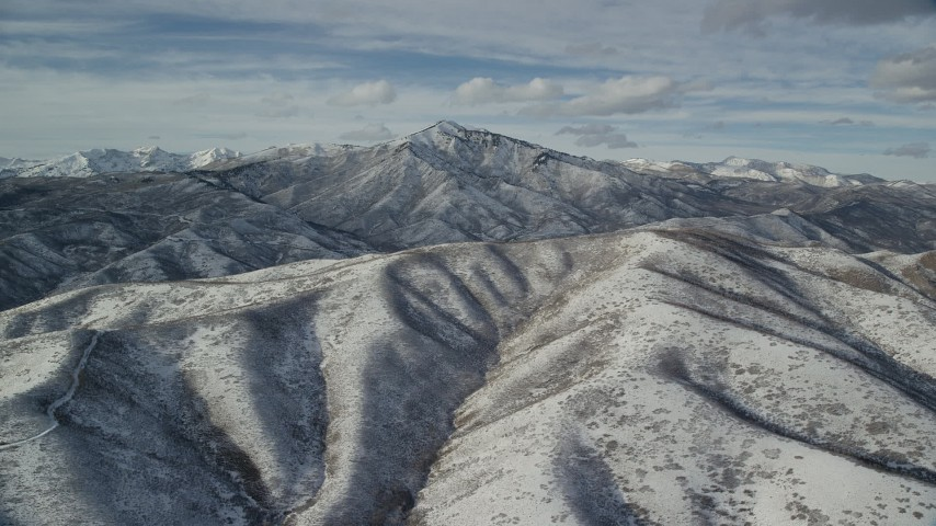 6K stock footage aerial video of Mill Canyon Peak seen from the top of a snowy mountain in winter, Wasatch Range, Utah Aerial Stock Footage | AX126_234
