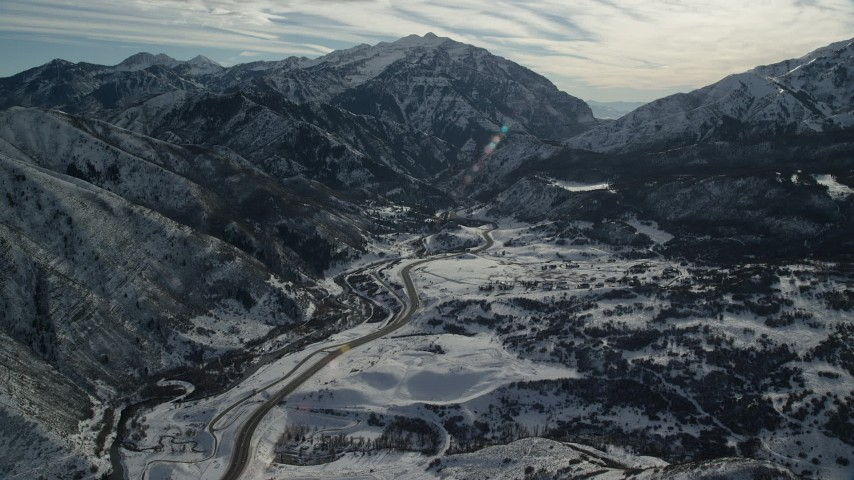 Approach Road at the Base of Snowy Mountains in Winter Aerial Stock Footage | AX126_235