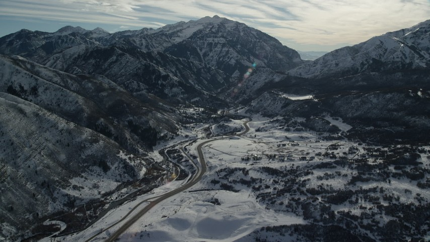6K stock footage aerial video approach road at the base of snowy mountains in winter, Wasatch Range, Utah Aerial Stock Footage | AX126_235