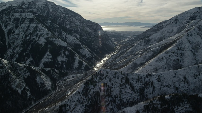 6K stock footage aerial video approach a road through Provo Canyon with winter snow on the mountains, Wasatch Range, Utah Aerial Stock Footage | AX126_242