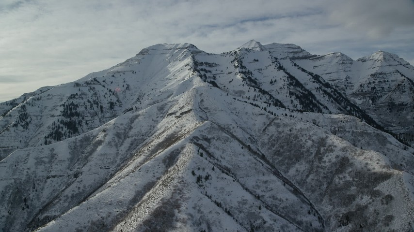 6K stock footage aerial video orbit of rugged Mount Timpanogos with winter snow in Utah Aerial Stock Footage | AX126_244