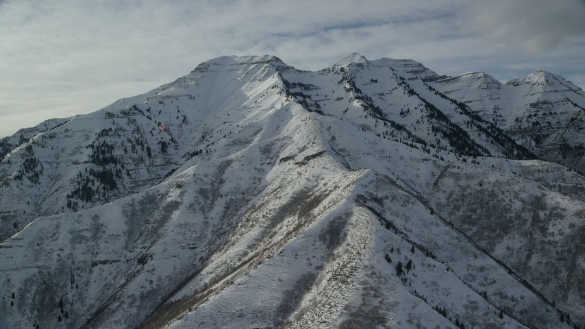 Orbit Giant Mountain Peaks Covered with White Winter Snow Aerial Stock Footage | AX126_245