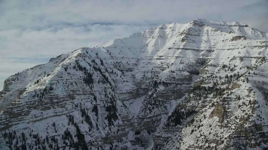 Orbit Snowy, Rugged Slopes of Mount Timpanogos in Winter Aerial Stock Footage | AX126_250