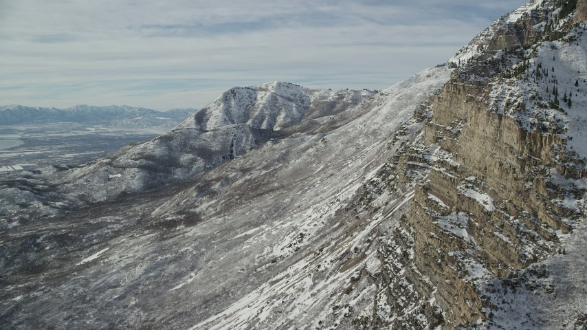 6K stock footage aerial video fly around jagged slopes of snowy Mount Timpanogos in winter, Utah Aerial Stock Footage | AX126_253