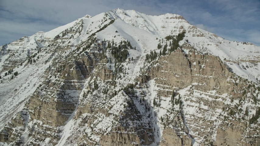6K stock footage aerial video orbiting steep slopes of Mount Timpanogos with winter snow, Utah Aerial Stock Footage AX126_255 | Axiom Images