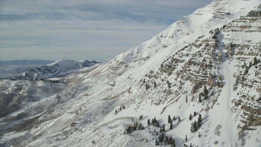 6K stock footage aerial video of flying over snowy, rugged slopes of Mount Timpanogos in Utah Aerial Stock Footage | AX126_258