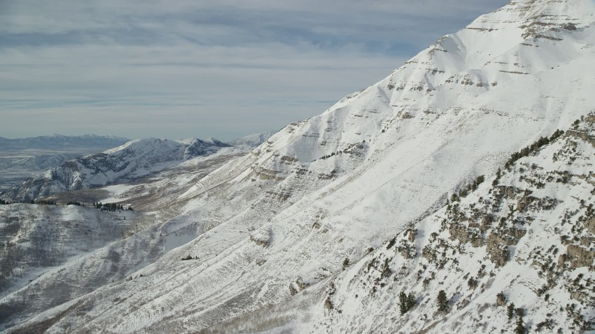 6K stock footage aerial video fly over snowy and rugged slopes of Mount Timpanogos in winter, Utah Aerial Stock Footage | AX126_259