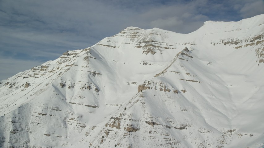6K stock footage aerial video of Mount Timpanogos slopes covered in winter snow in Utah Aerial Stock Footage | AX126_260