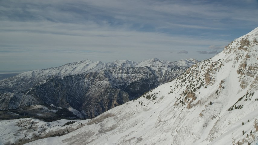 Approach Wasatch Range Snow Mountains seen from Mount Timpanogos Aerial Stock Footage | AX126_268